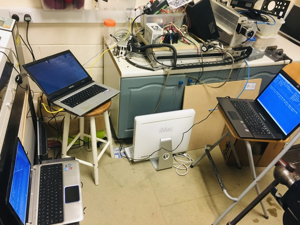 Three laptops on chairs accidentally positioned as if they were three people having a meeting together, in the process of wiping